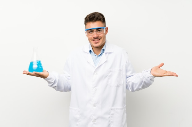 Young scientific holding laboratory flask over wall having doubts with confuse face expression