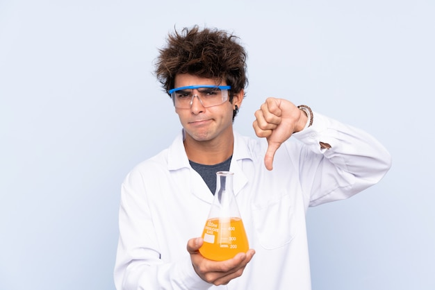 Young scientific man over isolated blue wall showing thumb down sign