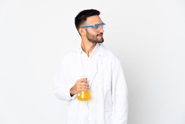 Молодой ученый человек изолирован на белом фоне, глядя в сторону и улыбается