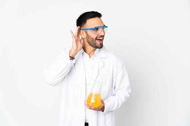 耳に手を置いて何かを聞いて白い壁に孤立した若い科学者