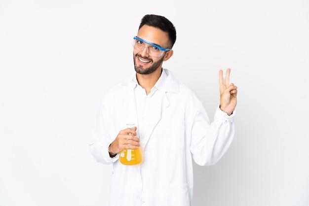 笑顔と勝利のサインを示す白い壁に孤立した若い科学者