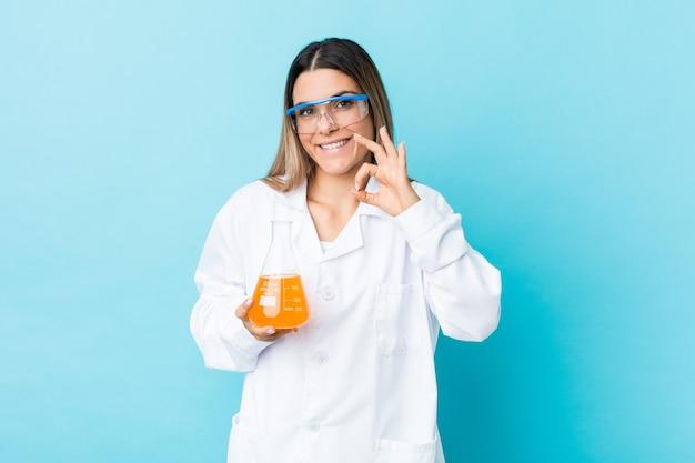 쾌활하고 자신감이 확인 제스처를 보여주는 젊은 과학 여자.