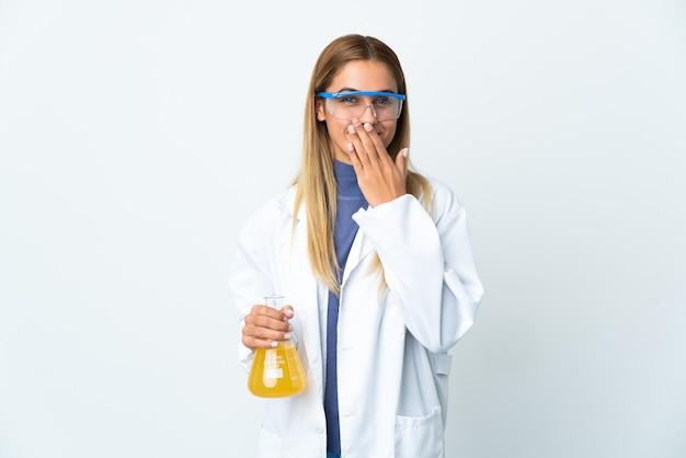 Молодая научная женщина, изолированная на белом пространстве, счастливая и улыбающаяся, прикрывая рот рукой