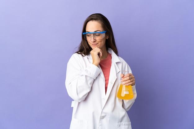 의심과 생각을 갖는 고립 된 배경 위에 젊은 과학 여자