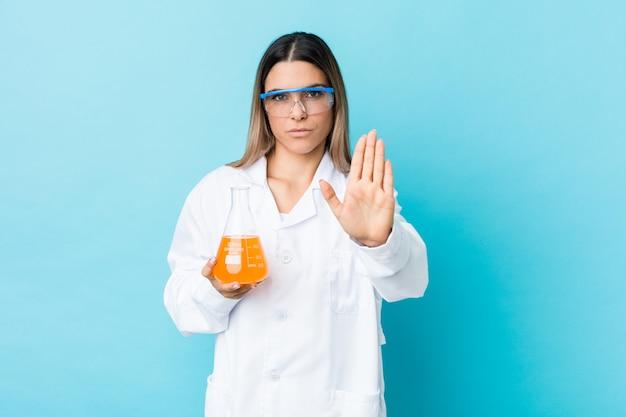 Молодая научная женщина, стоя с вытянутой рукой, показывая знак остановки