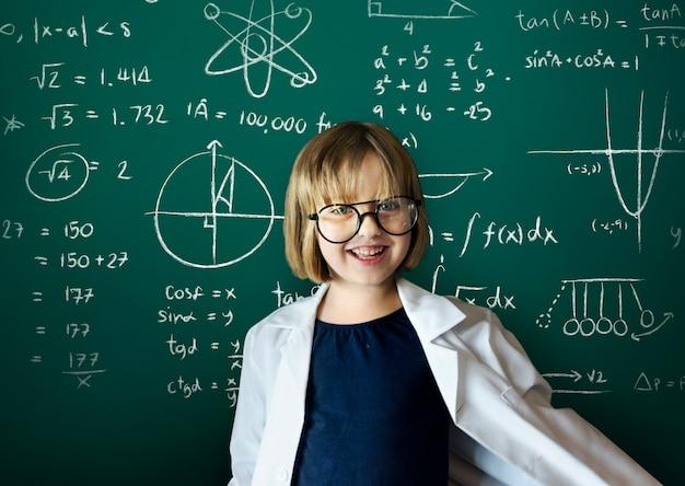 黒板の背景を持つ若い科学者の女の子