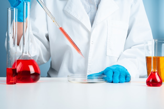 Young scientist with test tube making research in clinical laboratory
