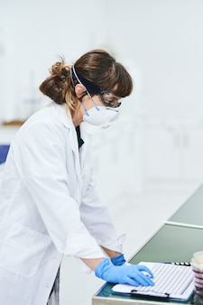 Young scientist woman in lab coat, goggles, gloves and safety mask working in the lab