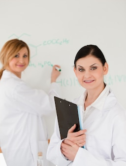 Young scientist writting a formula helped by her dark-haired assistant