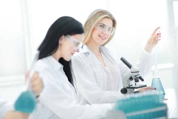若い科学者たちは実験室で液体をテストしています。科学と健康