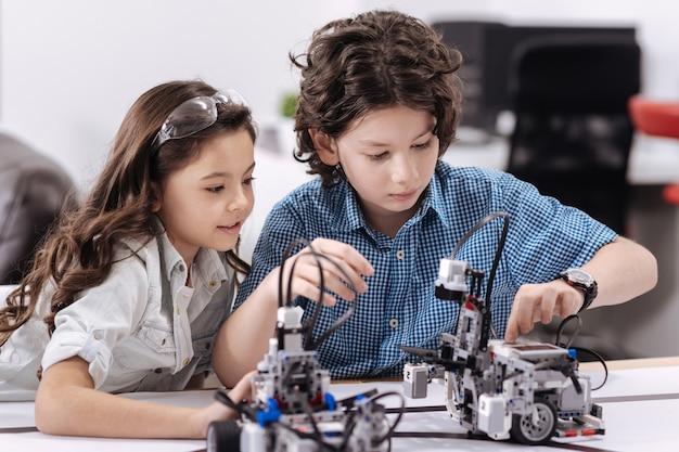 働いている若い科学者。学校に座って、ロボットに触れてプロジェクトに取り組んでいる間、技術クラスを楽しんでいる喜んで創造的な小さな科学者