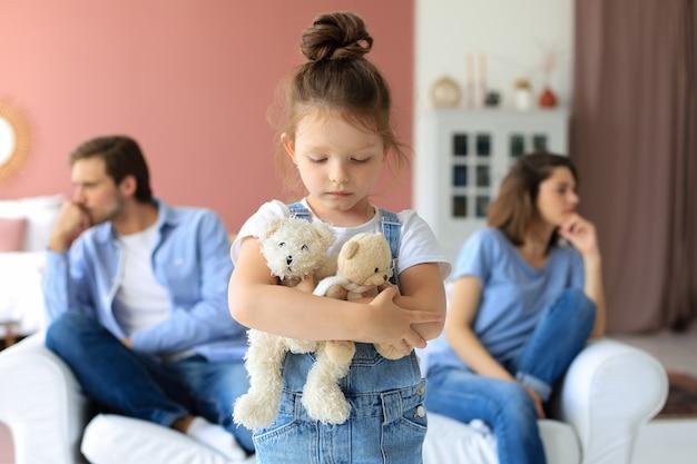 무방비 상태의 작은 딸이 카메라를 보며 화를 내는 동안 젊은 부모는 소파에 서로 반대편에 앉아 꾸짖었습니다. 프리미엄 사진