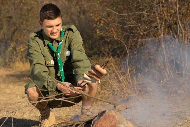 Молодой разведчик готовит свой обед на костре, когда он садится на корточки с партией сосисок, нанизанных на ветку, с нетерпеливой улыбкой