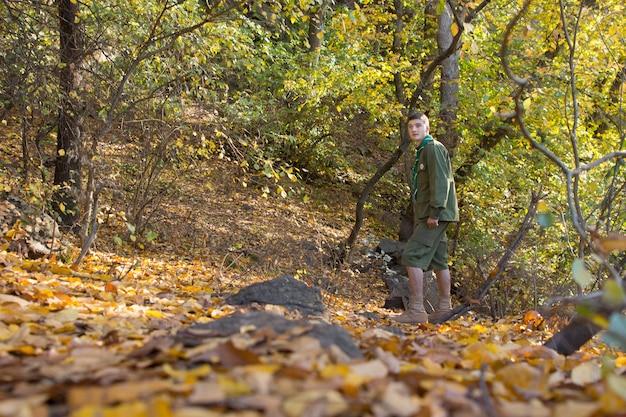 秋の森を歩いている制服を着た若いスカウトまたはレンジャーが、カメラを見渡すように向きを変え、彼の前にコピースペースがあります