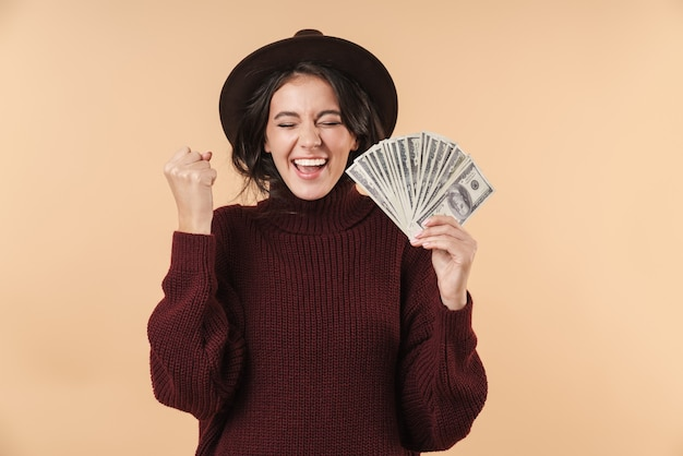Молодая кричащая эмоциональная брюнетка женщина, изолированная над бежевой стеной, держащей деньги, делает жест победителя.