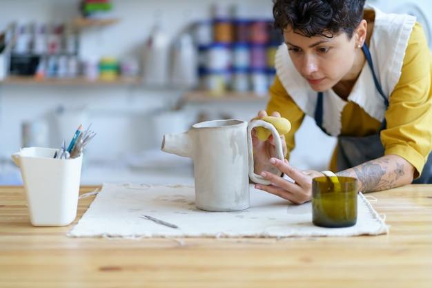 젊은 조각가 소녀는 젖은 점토로 작업하는 스튜디오 여성 도자기 예술가에서 세라믹 식기를 만듭니다.