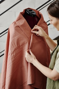 Молодая швея стоит у манекена, завернутого в кусок коричневой ткани, и сшивает его края перед шитьем нового предмета на машине