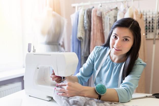 Молодая швея при швейная машина работая на ее офисе. концепция малого бизнеса