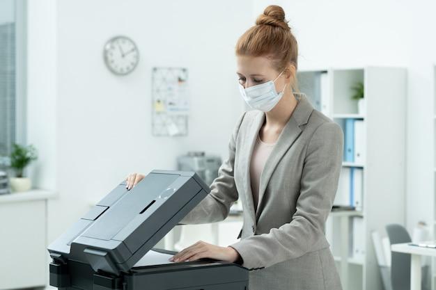 Молодой секретарь в сером костюме и защитной маске кладет бумагу в ксерокс, чтобы сделать копии на полках с документами в офисе