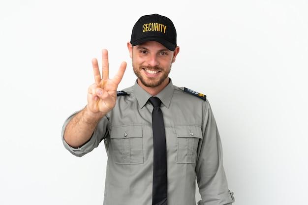 Молодой бразильский человек безопасности изолирован на белом фоне счастлив и считает три пальцами