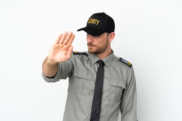 Молодой бразильский мужчина службы безопасности изолирован на белом фоне, делая жест стоп и разочарованный