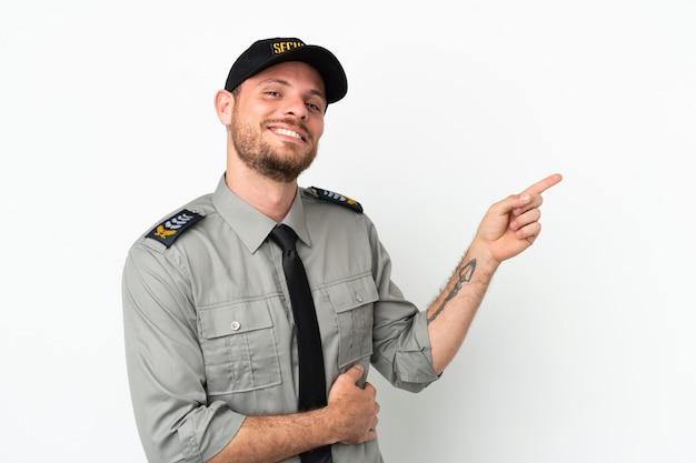 Молодой бразильский мужчина службы безопасности изолирован на белом фоне, указывая пальцем в сторону