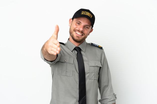 Молодой бразильский мужчина службы безопасности изолирован на белом фоне, пожимая руку для заключения хорошей сделки