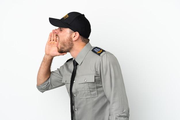 Молодой бразильский мужчина службы безопасности изолирован на белом фоне и кричит с широко открытым ртом в сторону