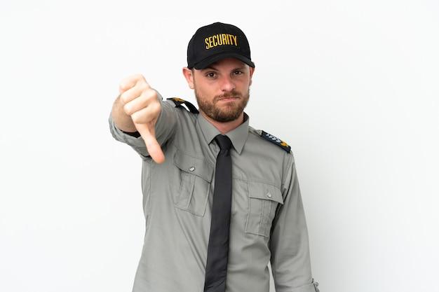 부정적인 표정으로 엄지손가락을 보여주는 흰색 배경에 고립 된 젊은 보안 브라질 남자