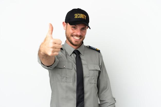 Молодой бразильский мужчина службы безопасности изолирован на белом фоне с большими пальцами руки вверх, потому что произошло что-то хорошее