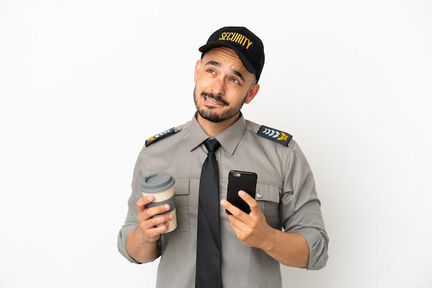 Кавказский молодой человек безопасности изолирован на белом фоне держит кофе на вынос и мобильный, думая о чем-то