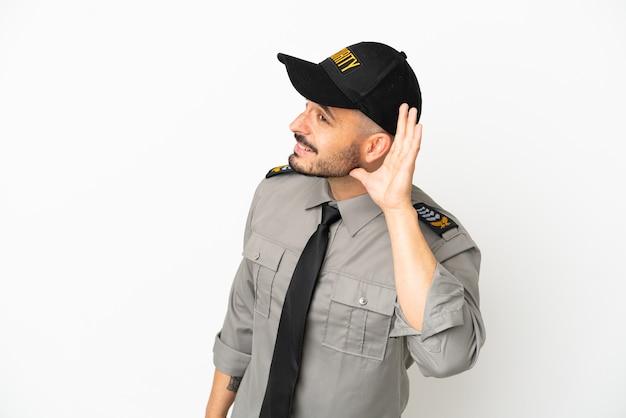 Кавказский молодой человек безопасности изолирован на белом фоне, слушая что-то, положив руку на ухо