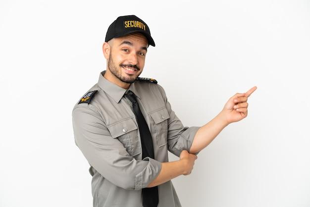 Молодой человек безопасности кавказской изолирован на белом фоне, указывая пальцем в сторону