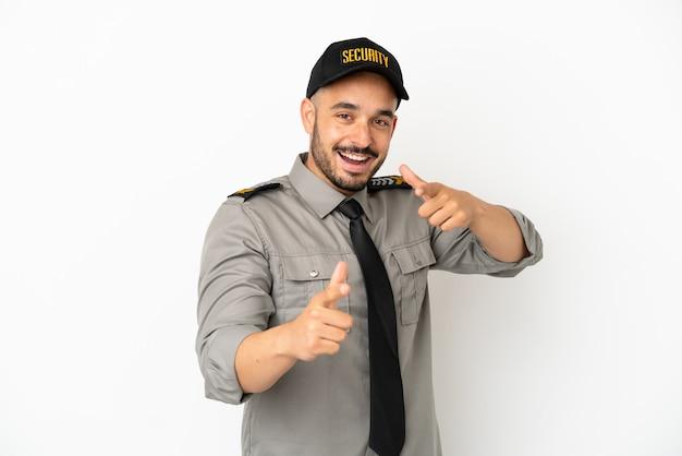 Кавказский молодой человек безопасности изолирован на белом фоне, указывая на фронт и улыбаясь
