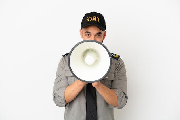 Молодой человек безопасности кавказской изолирован на белом фоне кричит через мегафон