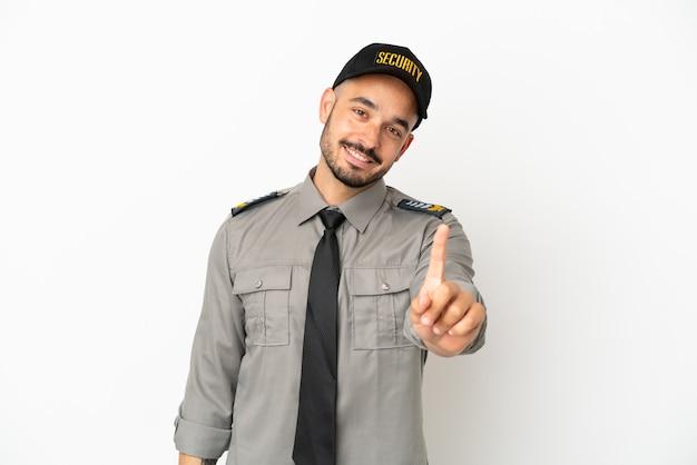Молодой человек безопасности кавказской изолирован на белом фоне, показывая и поднимая палец