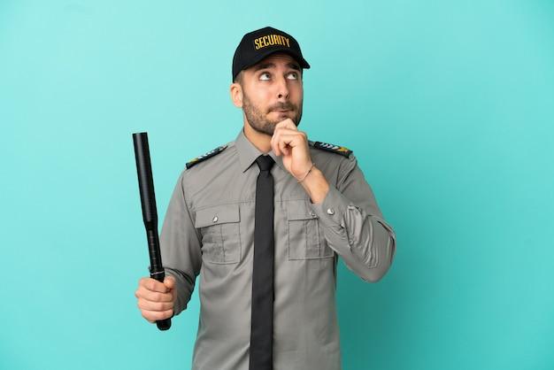 Молодой человек службы безопасности изолирован на синем фоне с сомнениями и мышлением
