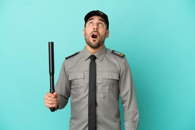 Молодой человек службы безопасности изолирован на синем фоне, глядя вверх и с удивленным выражением лица