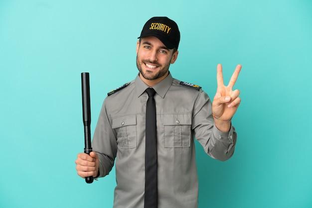 Молодой человек службы безопасности изолирован на синем фоне, улыбаясь и показывая знак победы