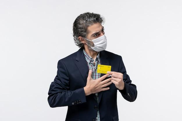 マスクを着用し、孤立した白い背景に彼の銀行カードを保持しているスーツの若い自己決定真面目なオフィスアシスタント