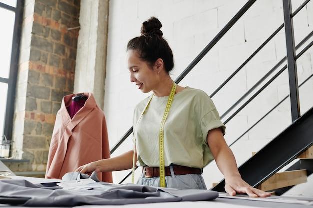 季節のコレクションアイテムのスケッチを見て、それらに適したテキスタイルを選択する若い自営業のファッションデザイナーまたはテーラー