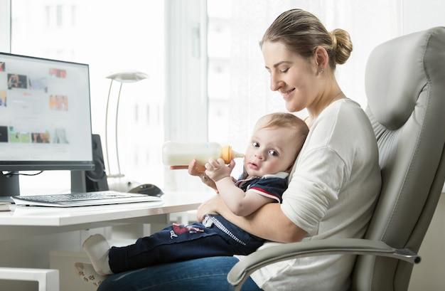 自宅で働き、赤ちゃんの世話をしている若い自営業の母親 Premium写真