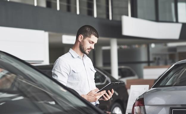 새 차를 판매하기위한 폴더가있는 젊은 판매자.