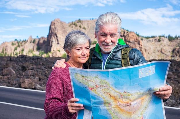 若い高齢者は一緒に旅行とアクティブなライフスタイルを楽しんでいます-道路で地図を探している老人と女性のカップル-代替の退職生活と山歩きの休日の休暇屋外