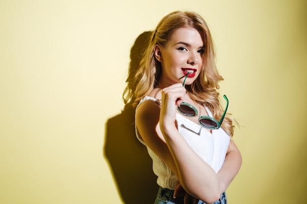 Young sensual blonde woman holding sunglasses and looking at camera