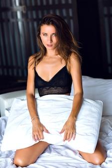 Giovane donna bruna sensuale che gioca con il cuscino, divertendosi al mattino, indossando una splendida lingerie nera sexy, stile boudoir