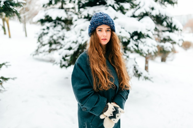 Young sensual girl in oversized coat with long beautiful hair standing in winter park with snowy spruces on background.
