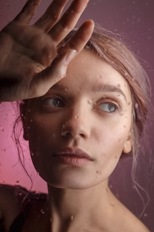 Young sensual girl puts her face on her hand and leans on glass on which blurred drops of water flow down. sad concept