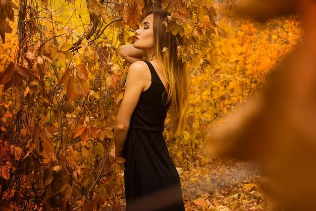 Молодая чувственная девушка с закрытыми глазами в черном платье позирует в золотом лесу на открытом воздухе
