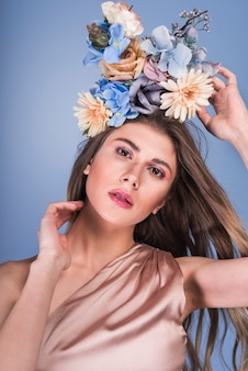 Young sensual lady in dress with beautiful flowers on head